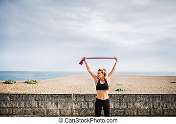 Young sporty woman runner with elastic bands outside on a beach in nature.