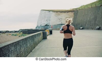 Young sporty woman runner with smartphone running on the...