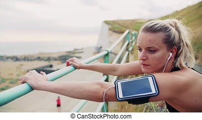 Young sporty woman runner with smartphone stretching on the beach outside.