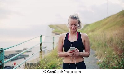 Young sporty woman runner with smartphone walking on the beach outside.