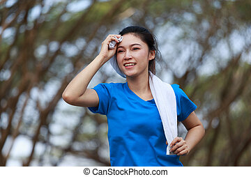 young sporty woman running and wiping her sweat with a towel in park