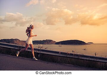 Young sporty woman running outdoor at sunset.