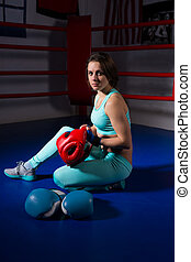 Young sporty woman sitting near lying boxing gloves and helmet