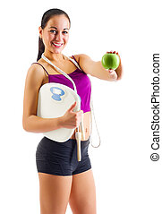 Young sporty woman with apple and scales