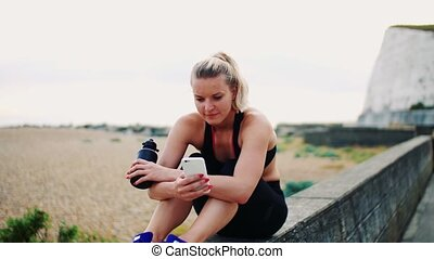 Young sporty woman with smartphone sitting outside, texting....