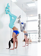 Young sporty women doing handstand exercise. Athletic girls...