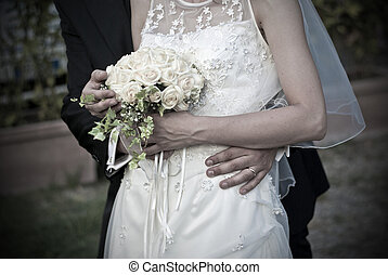 young spouses play with love rings that they have given and with the bouquet