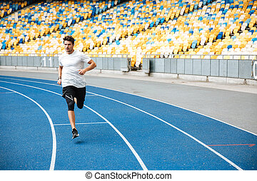 Young sprinter running on athletics track