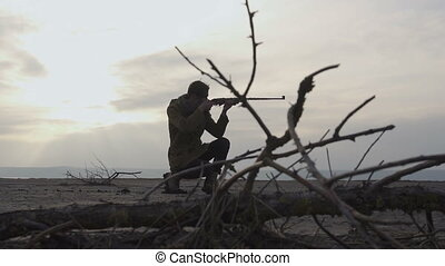 Young Stalker guy with rifle taking aim in cloudy post apocatyptic wasteland. Stalker - Survival concept