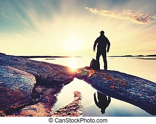 Young standing man with backpack. Hiker on the stone on the seashore at colorful sunset sky.
