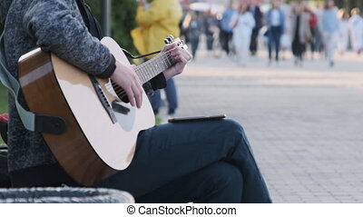 Young Street Musician Playing Acoustic Guitar in the Park. People Walk By