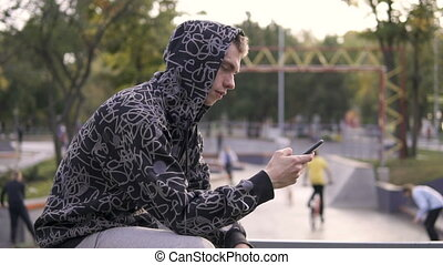 Young streetstyle man in hoodie using his smartphone in hood, Sitting on the fence of skatepark