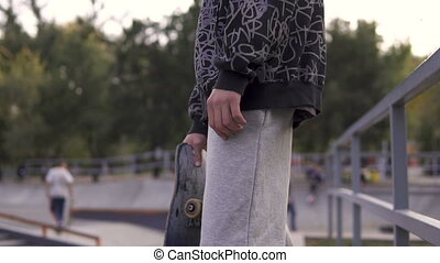 Young streetstyle man stays with skateboard on the border of skatepark in autumn city