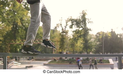 Young streetstyle man walk by railing on the border of skatepark in autumn city.