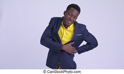 Young stressed African businessman having back pain