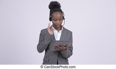 Young stressed African businesswoman as call center representative using digital tablet