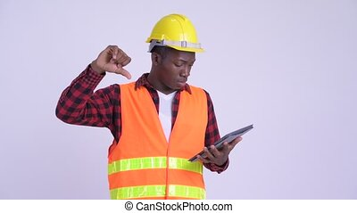 Young stressed African man construction worker using digital tablet and getting bad news
