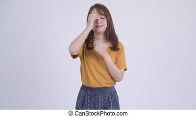 Young stressed Asian woman getting bad news - Studio shot of...