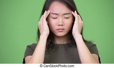 Young stressed Asian woman having headache