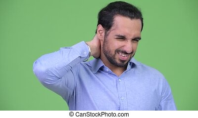Young stressed bearded Indian businessman having neck pain -...