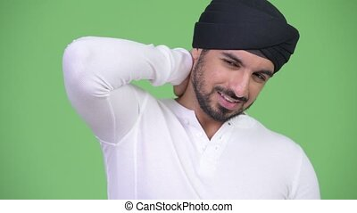 Young stressed bearded Indian man having neck pain - Studio...