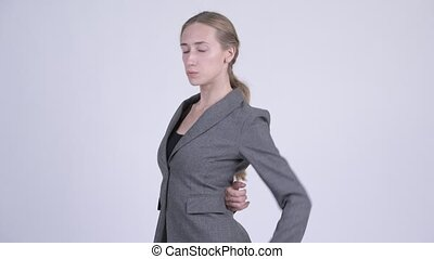 Young stressed blonde businesswoman having back pain -...