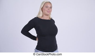Young stressed blonde woman having back pain - Studio shot...