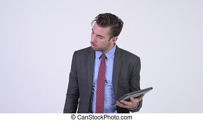 Young stressed Hispanic businessman using digital tablet and getting bad news