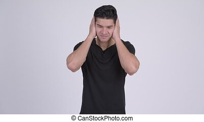 Young stressed multi-ethnic man covering ears - Studio shot...