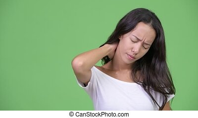 Young stressed multi-ethnic woman having neck pain - Studio...