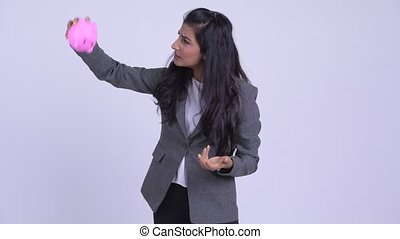 Young stressed Persian businesswoman shaking piggy bank and...