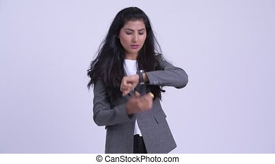 Young stressed Persian businesswoman waiting and checking time