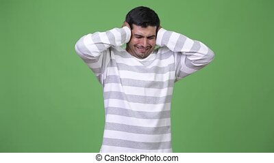 Young stressed Persian man covering ears from loud noise -...