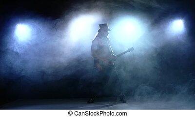 Young strip man playing bass guitar. Slow motion. smoke