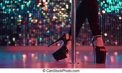 Young stripper dances in high heels shoes near pole in night...
