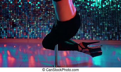 Young stripper in black dances sexually with pylone in night men's club. Poledance. Close-up legs of unrecognizable woman doing tricks with pole.