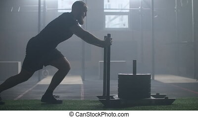 Young strong athletic Caucasian man exercising with heavy weight training sled towards camera in large gym slow motion