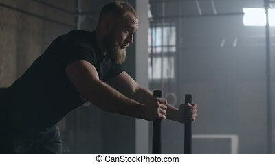 Young strong athletic Caucasian man exercising with heavy weight training sled towards camera in large gym slow motion.