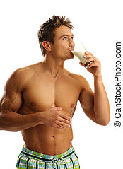 An attractive strong man drinking milk from glass
