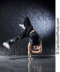 Young strong man break dance. On dark wall background.