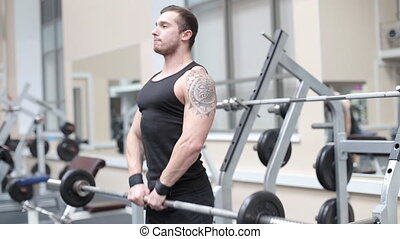 Young strong man hard train muscles in gym