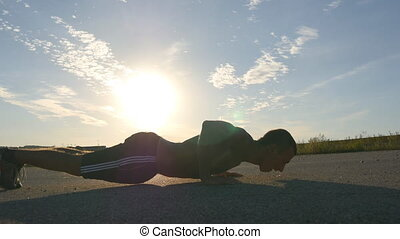 Young strong man making pushups outdoor. Fit muscular male fitness guy warming up before running. Athlete training push-up on country road at sunset. Healthy active workout lifestyle. Close-up.