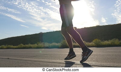 Young strong man running on countryside path. Male runner jogging during workout training on country road at sunset. Handsome athletic male working out in summer. Training outdoors. Active lifestyle.