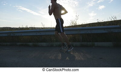 Young strong man running on road in beautiful nature. Male runner jogging during workout training on country road at sunset. Handsome athletic male working out in summer. Training outdoors Slow Motion