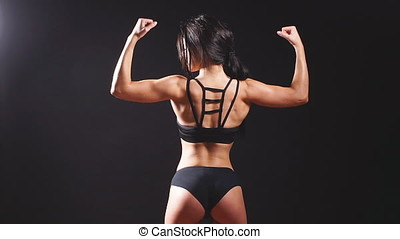 Young strong sexy woman showing her muscles. - Athletic...