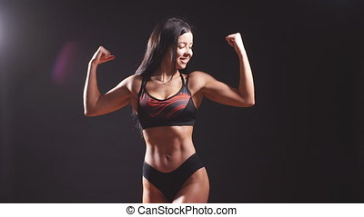 Young strong sexy woman showing her muscles. - Young strong...