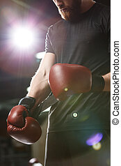 Young strong sports man boxer in gym