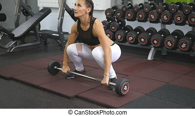 Young strong woman with fitness body in sportswear snatches heavy weight in gym. Female bodybuilder doing exercise - practicing deadlift at health club. Girl training - lifting barbell. Slow motion