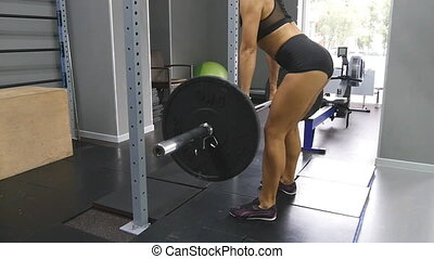 Young strong woman with perfect fitness body in sportswear lifts barbell and throws it in gym. Heavy barbell falls on the floor. Girl practicing deadlift at health club. Female training. Slow motion.