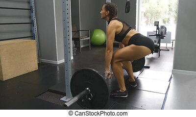 Young strong woman with perfect fitness body in sportswear...